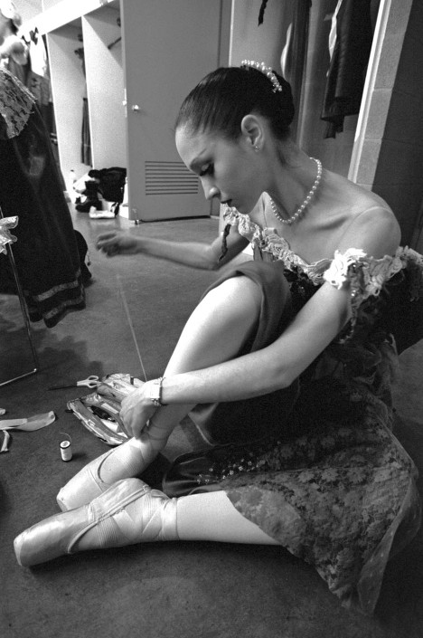 A ballerina from the Royal Flanders Ballet adjusts her pointe shoes.