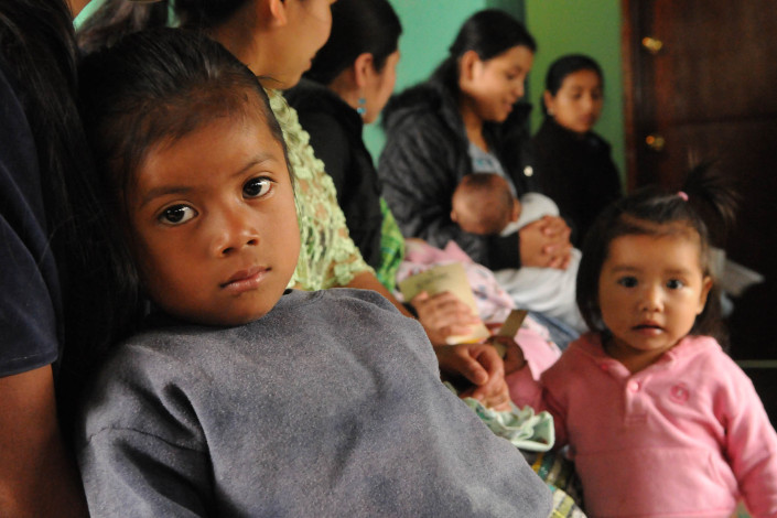 An indigenous Mayan girl waits with her mother and siblings, for a routine health checkup at a health center in rural Guatemala.