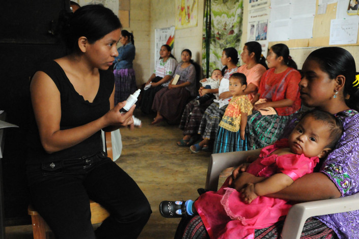 A health worker holding a bottle of medication, advises an indigenous Mayan woman holding her 1-year-old daughter, about the correct use of acetaminophen, in rural Guatemala.