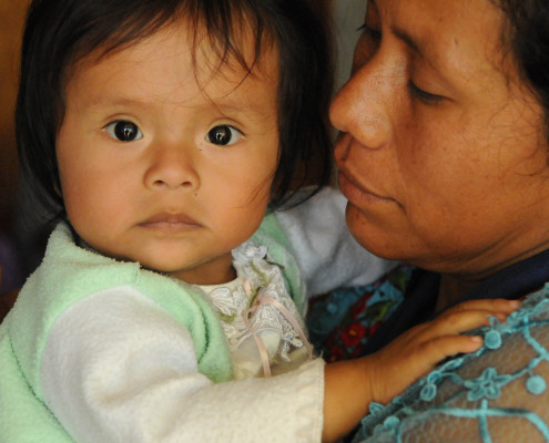 An indigenous Mayan woman holds her wide-eyed infant daughter in a health center in rural Guatemala.