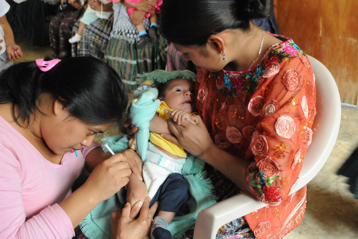 A health worker administers a pentavalent vaccine injection to a 3-month-old infant in rural Guatemala.