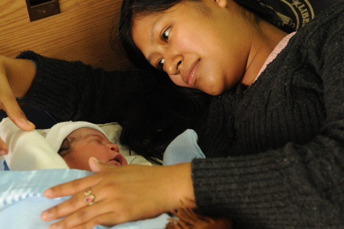 An indigenous Mayan woman cradles her newborn son at Coban Hospital in Guatemala.