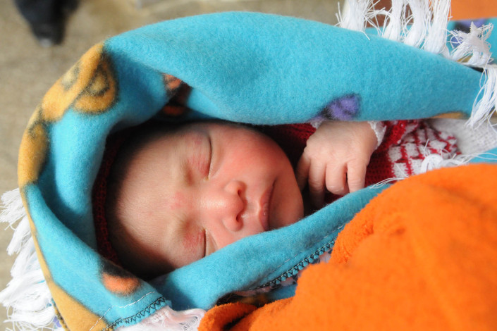 Swaddled in blankets and sleeping, a 1-day-old infant is held by his father, an indigenous Mayan man in Guatemala.