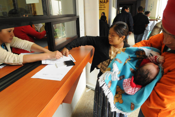 A health worker assists an indigenous Mayan woman, who has just given birth, as she puts her thumbprint on birth registration papers for her newborn son, as her husband stands nearby holding their son.