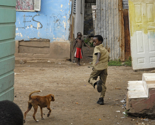 Children play outside their home as a dog walks nearby, in the community of Trenchtown in Kingston, Jamaica.