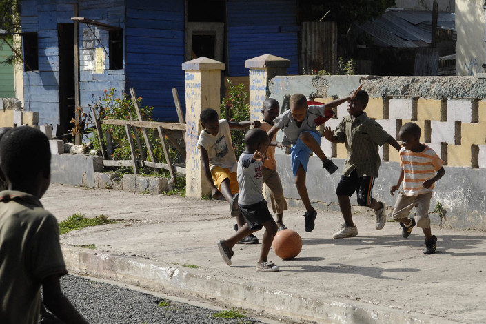 A group of boys play football or soccer on a Trenchtown street in the parish of Kingston and St. Andrew, Jamaica.
