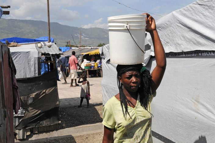 A woman carries a bucket of clean water on her head in Carrefour Aviation in Port-au-Prince, Haiti.