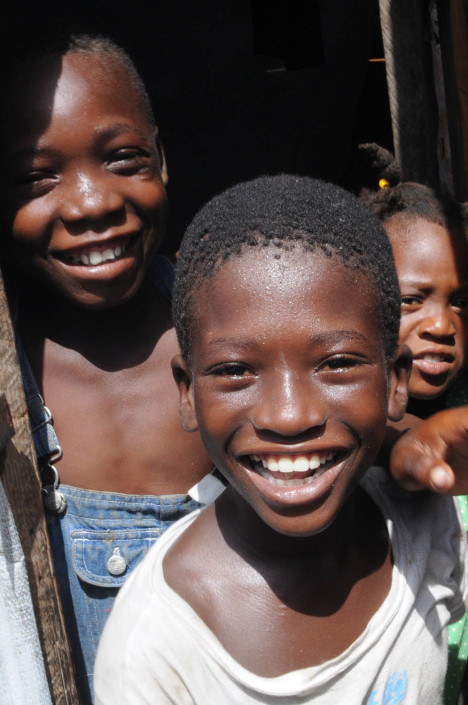Displaced children smile in Carrefour Aviation after the 2010 Haiti earthquake.