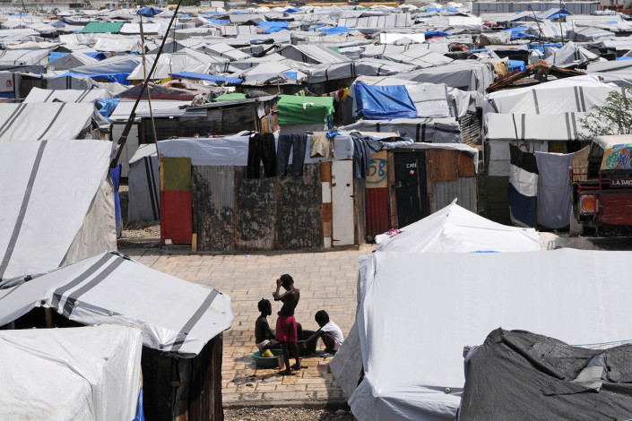 Displaced persons bathe amid tents in Carrefour Aviation, a tent camp for displaced persons in Haiti