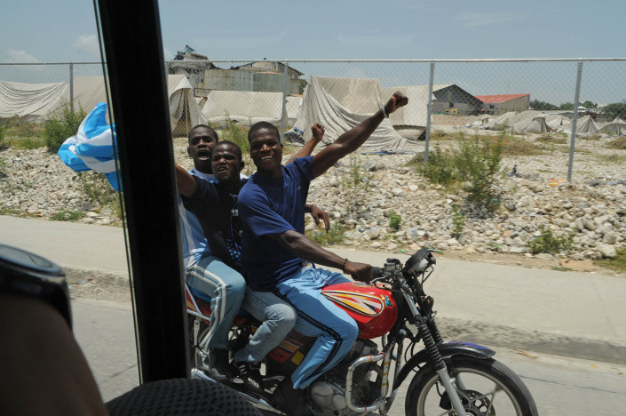 Fans ride alongside the convoy of Footballer and UNICEF Goodwill Ambassador Lionel 'Leo' Messi in Port-au-Prince, Haiti.