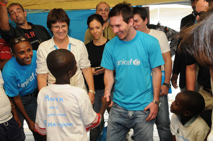 UNICEF Goodwill Ambassador Lionel 'Leo' Messi (centre) greets children at the UNICEF office in Port-au-Prince, Haiti, six months after the 2010 earthquake.