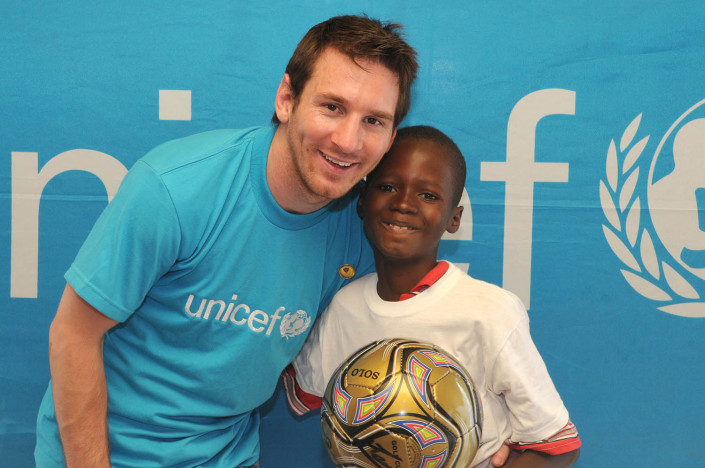UNICEF Goodwill Ambassador Lionel 'Leo' Messi stands with 12-year-old Rikelme Marseil, who is holding a football, at the UNICEF office in Port-au-Prince, Haiti.
