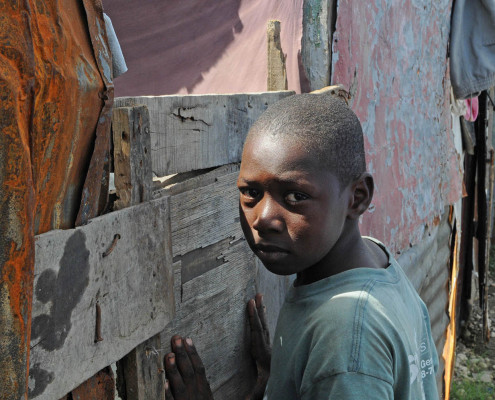 A boy leans against his makeshift home after the earthquake in Port-au-Prince, Haiti.