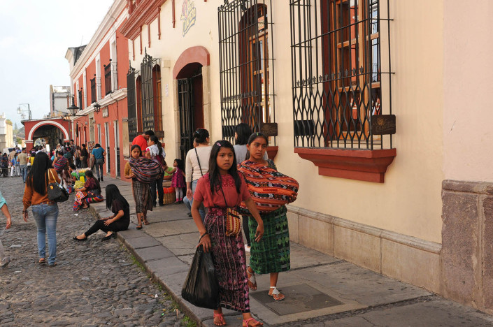 Two girls walk down a street in Antigua, Guatemala.