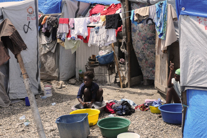 A woman washes clothing outside her makeshift home at Carrefour Aviation, a tent-camp, in Port-au-Prince, Haiti, after the June earthquake that killed more than 225,00 and displaced more than two million people.