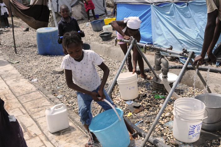 A girl collects water from a pump in Carrefour Aviation, a tent camp housing 50,000 people who were displaced by the earthquake in Haiti,