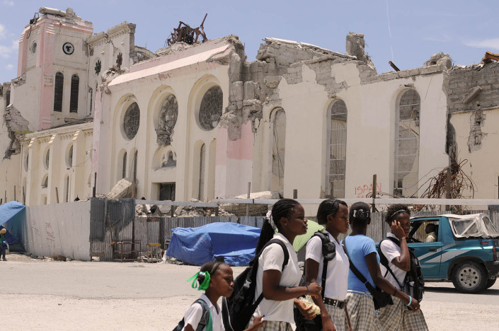 A group of adolescent girls walk to school past homes devastated by the 7.3 magnitude earthquake which took place on 12 January 2010, in Port-au-Prince, Haiti.