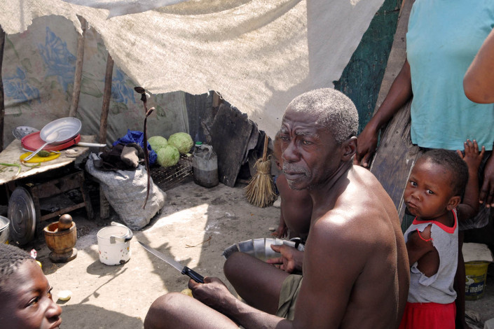 A man prepares a meal at Carrefour Aviation, a tent camp housing 50,000 people who were displaced by the 7.3 magnitude earthquake on 12 January in Haiti.