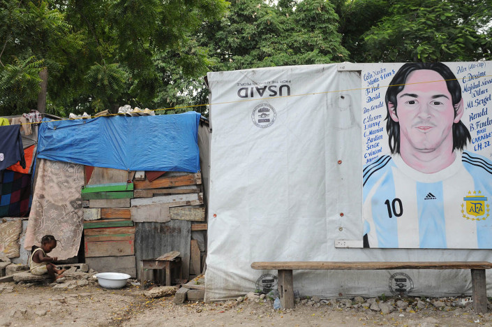 A child plays outside a makeshift tent bearing a portrait of Argentinean football player Lionel Messi, in Port-au-Prince, Haiti.