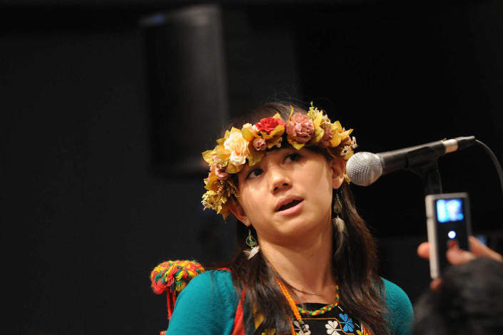 A girl wearing a floral headpiece speaks at an indigenous forum.