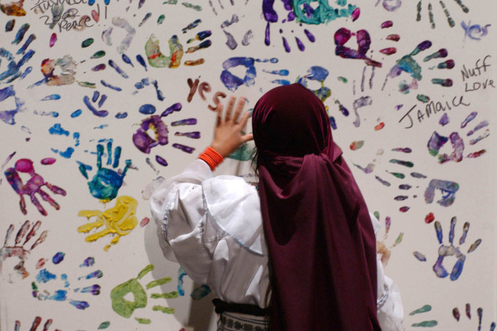 A girl places her painted handprint on a large painting.