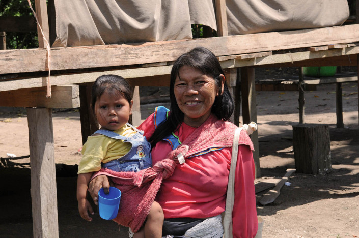 A woman holds her young daughter outside their home in the indigenous community of Nuevo Saposoa in the Peruvian Amazon.