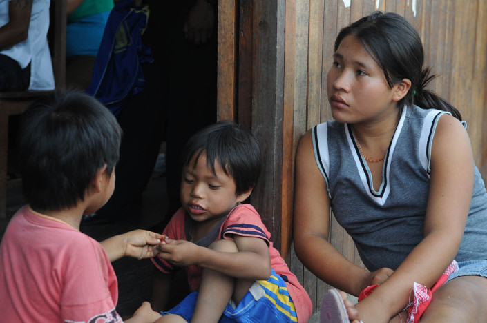 An adolescent girl and 2 young children sit outside a community center in the indigenous Shipibo-Conibo community of Nuevo Saposoa in the Peruvian Amazon.