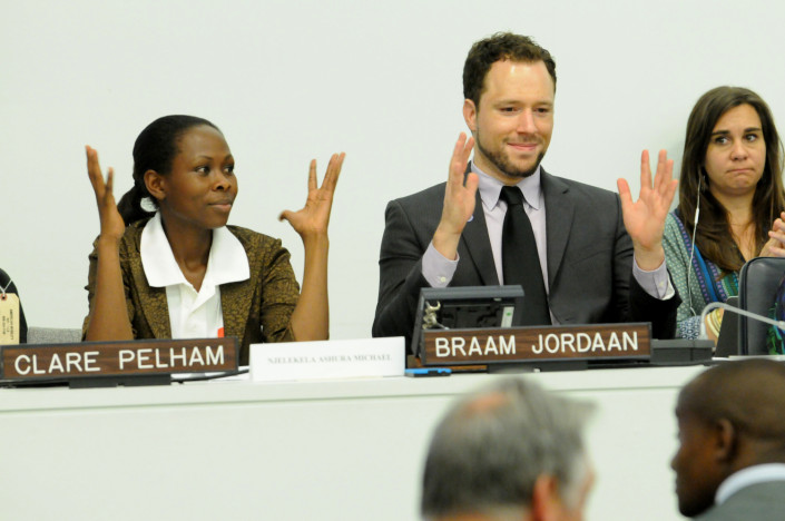 Disability activists at the UN sign their applause in sign language at a conference.