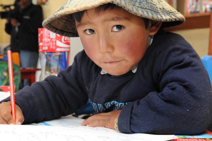 A boy sits at his desk in a classroom at Robertito School at the Cerro Rico Mines in the city of Potosí, Bolivia.