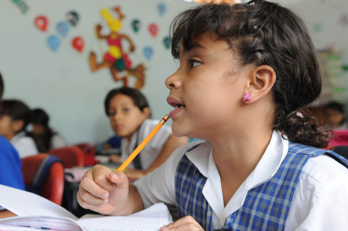 A girl holding a pencil, sits in a Spanish class in Medellín, Colombia.
