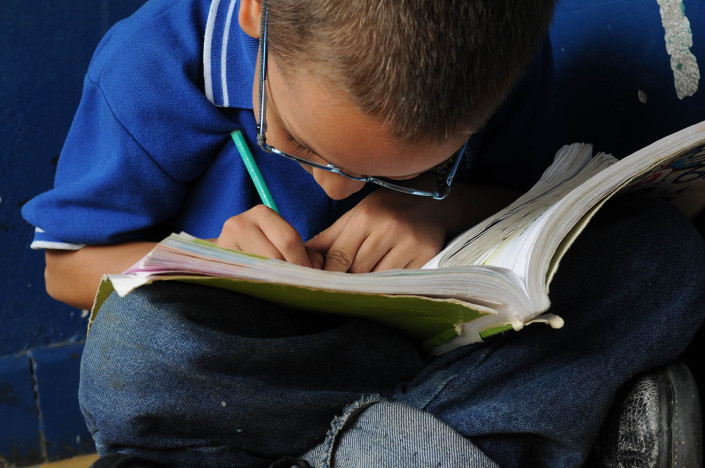 A boy writes in his notebook outside a classroom in Medellín, Colombia.