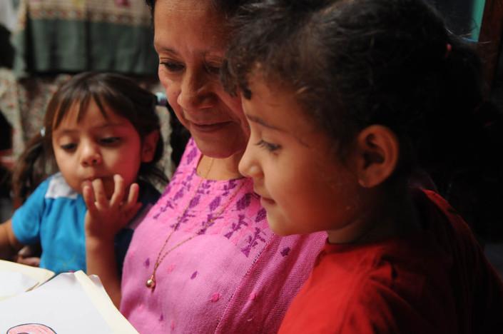 Children sit with their foster mother in their kitchen, in Guatemala.