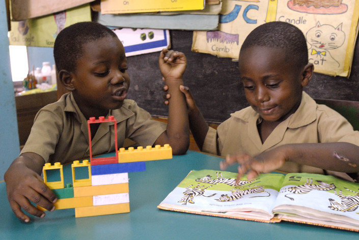 A boy plays with colourful plastic blocks while another boy views a book on counting at a school in the parish of Kingston and St. Andrew, Jamaica.