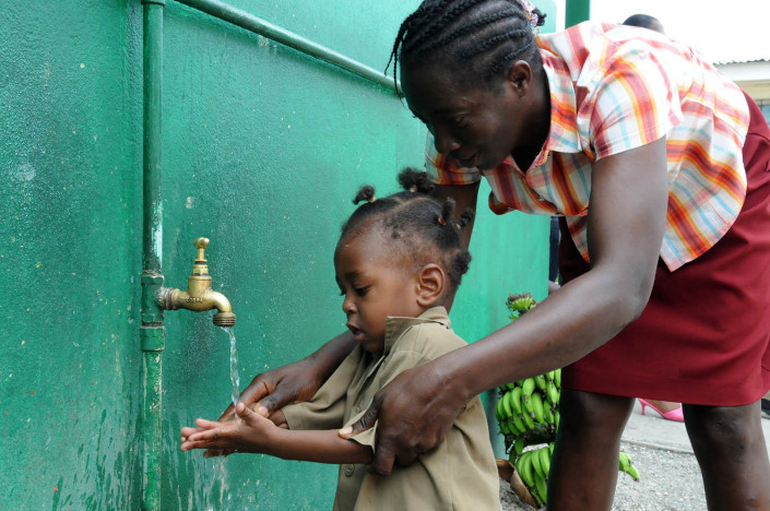 A teacher helps a toddler wash his hands at an outdoor water point outside a school in the parish of Kingston and St. Andrew, Jamaica.