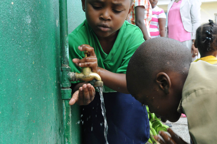 Children wash their hands and faces at an outdoor water point.