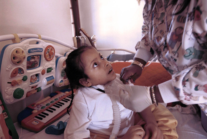 A nurse removes secretions from the ventilator of a boy with Spina Bifida.