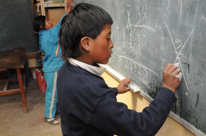 Children write on the blackboard at a school at the Cerro Rico Mines in Potosí, Bolivia.