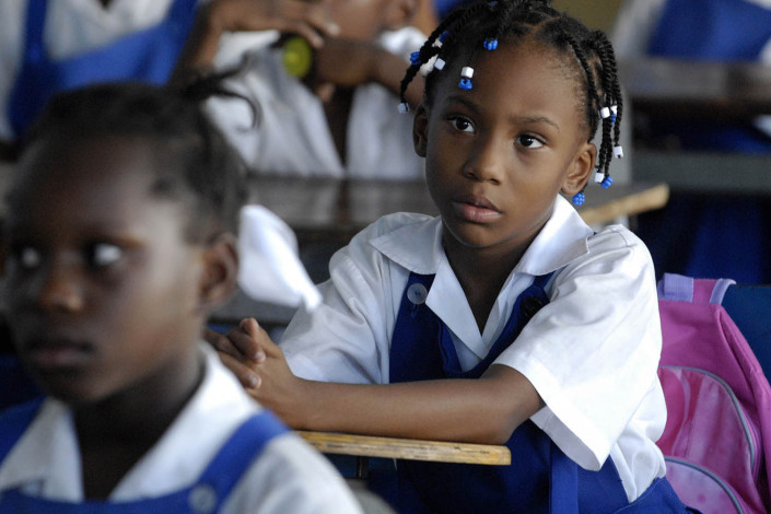 Girls listen to a discussion at a primary school in Jamaica.