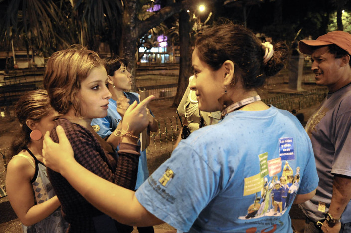An outreach worker tries to convince a n adolescent girl on a street in Colombia to accompany her to a shelter.