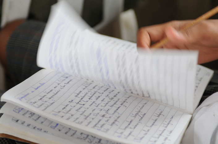 A girl flips through her science notebook at her school in Lorica, Colombia.
