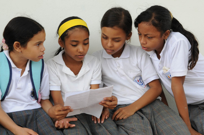 Girls discuss work together outside their classroom in Lorica, Colombia.