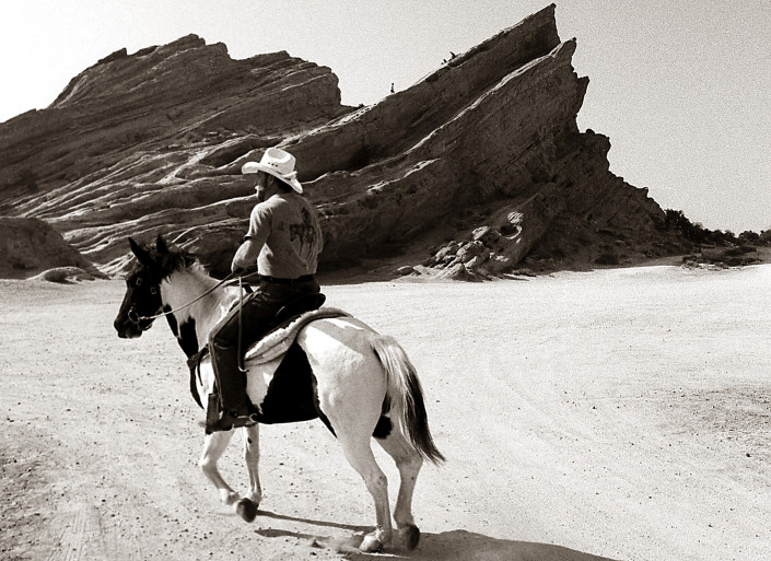 Man with white cowboy hat rides his Palomino horse near Vasquez Rocks in California.