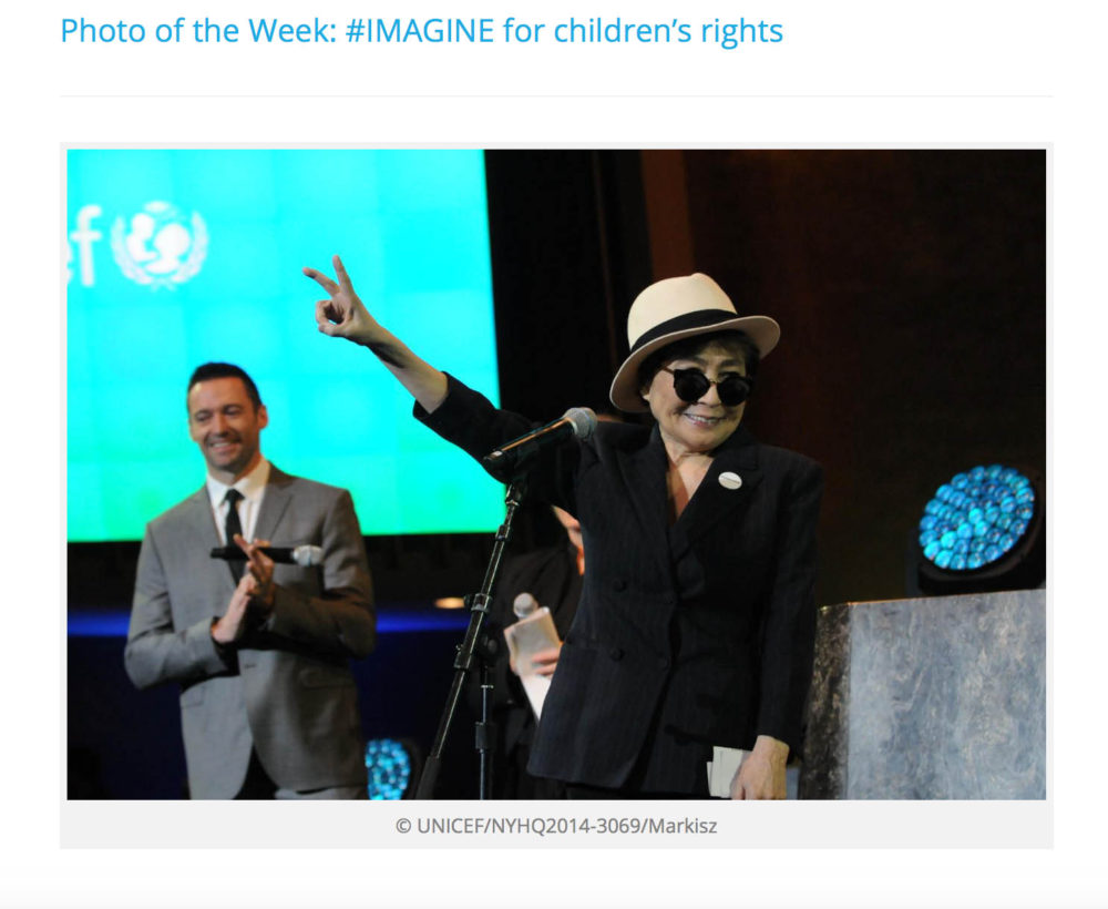 Yoko Ono gives the peace sign at the United Nations as actor Hugh Jackman stands behind her.