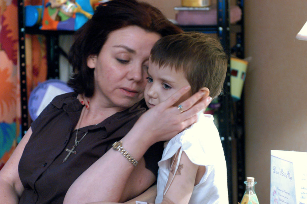 """Robyn Brooks, 7, and her mom Karen, share a tender moment during Robyn's painful treatments for neuroblastoma. Beside her is a greeting card that says """"Don't Give Up."""""""