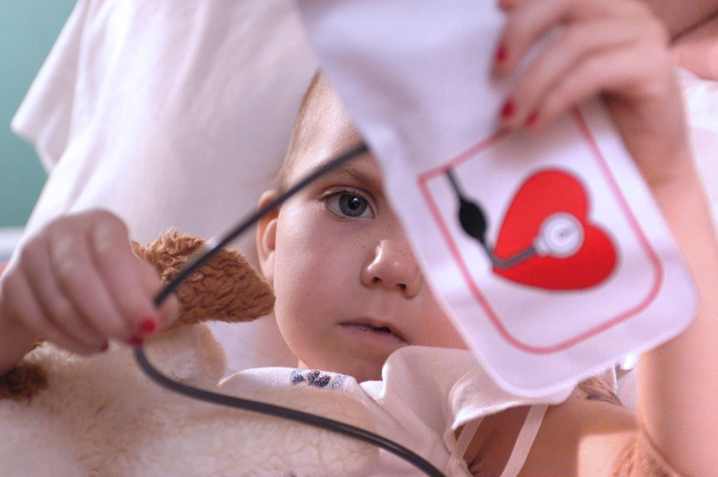 Robyn Brooks, 7, holds a toy blood pressure cuff, and her stuffed toy named Patch during treatments for neuroblastoma.