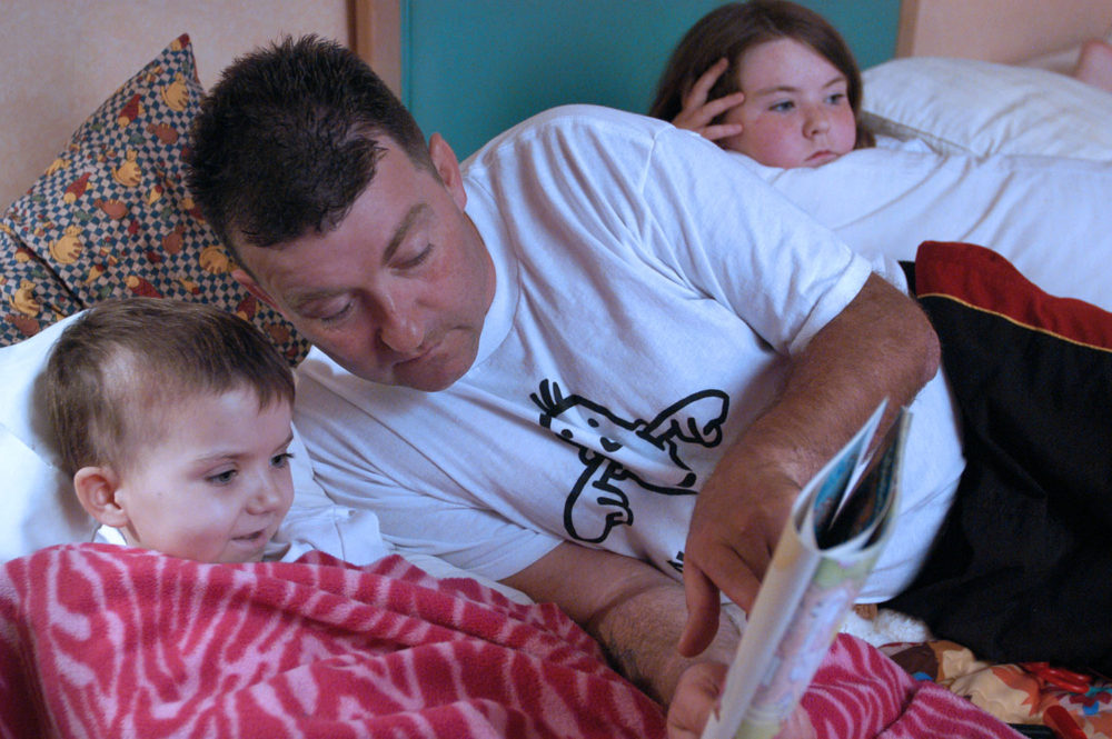 Garry Brooks reads to his daughter Robyn, wrapped in a blanket, in their temporary home at the Ronald McDonald House. She is being treated for neuroblastoma.