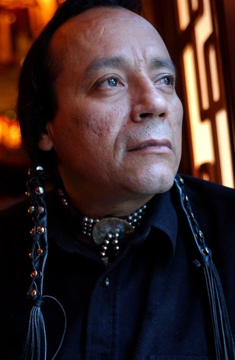 Portrait of native American man with long leather wrapped braids, wearing silver neckwear, next to a window.