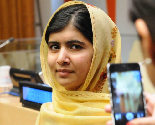 Education activist Malala Yousafzai, wearing a yellow dress and head covering, at the UN.
