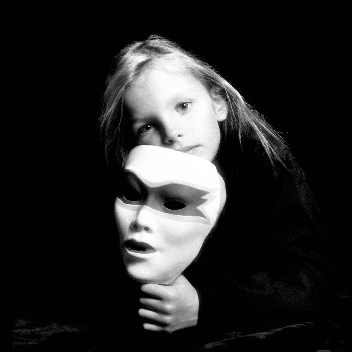 A 7-year-old girl holds a white mask mirroring her features in a studio portrait.