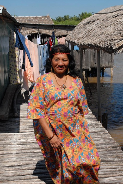 An indigenous woman advocate wearing a colorful dress, stands outside a typical Anu dwelling above a lagoon in Venezuela.